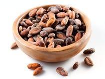 Granos de cacao en el crisol de madera aislado Fotos de archivo