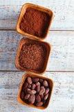 Granos de cacao, polvo y chocolate rallado en los cuencos de madera, blancos Foto de archivo