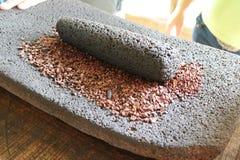 Granos de cacao puestos a tierra en una pizarra de piedra Fotografía de archivo