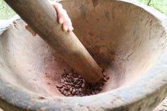 Granos de cacao que son puestos a tierra en un mortero Fotos de archivo
