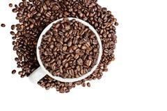 Granos de café aislados que desbordan de una taza Fotos de archivo