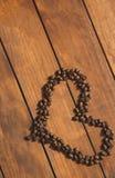 Granos de café aromáticos en forma de corazón en el escritorio Fotos de archivo libres de regalías