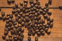 Granos de café aromáticos que localizan en el escritorio Foto de archivo libre de regalías
