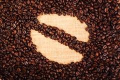 Granos de café asados con el fondo de la arpillera Fotografía de archivo libre de regalías