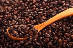 Granos de café asados con la cuchara de madera, opinión del primer Imágenes de archivo libres de regalías