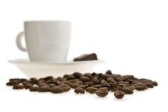 Granos de café asados con una taza del café con leche Imágenes de archivo libres de regalías