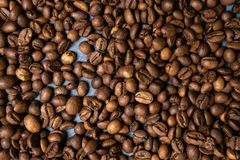 Granos de café asados en bulto en un fondo azul fotografía de archivo