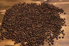 Granos de café asados en bulto en un fondo de madera fotos de archivo libres de regalías