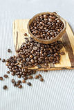 granos de café asados en cáscara del coco en el fondo de madera rústico, aún fotografía de la vida con los granos de café asados Imágenes de archivo libres de regalías