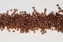 Granos de café asados en el fondo blanco foto de archivo libre de regalías