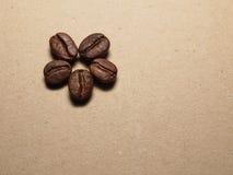 Granos de café asados en la textura de papel Imagenes de archivo