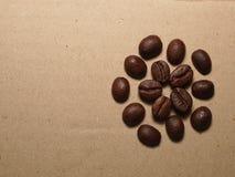 Granos de café asados en la textura de papel Imagen de archivo libre de regalías