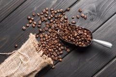 Granos de café asados en saco y pala en la tabla fotos de archivo libres de regalías