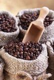 Granos de café asados en sacos de la arpillera Fotos de archivo