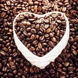 Granos de café asados en un cuenco en forma de corazón en Valentine Day Ho Fotografía de archivo