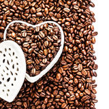 Granos de café asados en una caja en forma de corazón blanca en la tarjeta del día de San Valentín D Foto de archivo