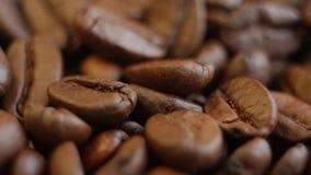 Granos de café asados en una tabla rotating Cierre para arriba metrajes