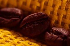 Granos de café asados, fragantes macros en fondo amarillo Fotografía de archivo libre de regalías