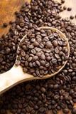 Granos de café asados frescos en una cucharada Foto de archivo