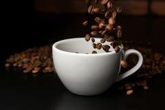 Granos de café asados que caen en la taza Imagen de archivo