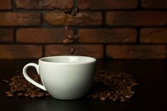Granos de café asados que caen en la taza Fotos de archivo