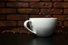 Granos de café asados que caen en la taza Foto de archivo