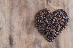 Granos de café asados, símbolo del corazón en fondo de madera Foto de archivo libre de regalías