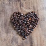 Granos de café asados, símbolo del corazón en fondo de madera Fotos de archivo