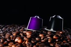 Granos de café asados y dos cápsulas sobre negro fotografía de archivo