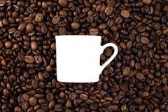 Granos de café asados y una taza de la silueta fotografía de archivo libre de regalías