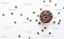 Granos de café brillantes en una taza con el texto del café en otros idiomas Papel pintado internacional del café Imagen de archivo