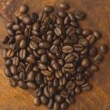 Granos de café de Brown en forma del círculo, primer de los granos de café macros para el fondo y textura En el tablero de madera Fotos de archivo libres de regalías