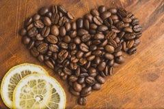 Granos de café de Brown en la forma del corazón con el limón, el primer de los granos de café macros para el fondo y la textura E Imagenes de archivo