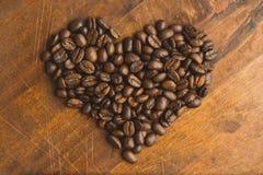 Granos de café de Brown en la forma del corazón, del primer de los granos de café macros para el fondo y de la textura En el tabl Fotos de archivo