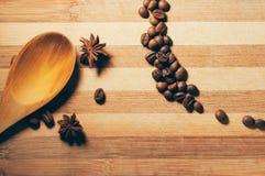 Granos de café con anís y la cuchara de madera fotografía de archivo