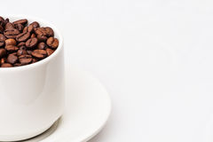 Granos de café con la taza de café blanca Fotos de archivo