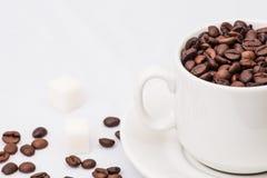 Granos de café con la taza de café blanca Fotografía de archivo