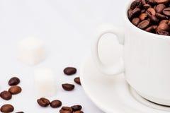 Granos de café con la taza de café blanca Imágenes de archivo libres de regalías