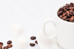 Granos de café con la taza de café blanca Fotos de archivo libres de regalías