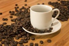 Granos de café con la taza del café express del Demitasse Imagenes de archivo