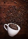 Granos de café con la taza en una tabla Imagen de archivo libre de regalías