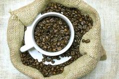 Granos de café con la taza y el platillo Fotos de archivo libres de regalías