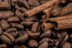 Granos de café con los palillos de canela en la materia textil del saco Imágenes de archivo libres de regalías