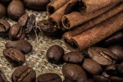 Granos de café con los palillos de canela en la materia textil del saco Foto de archivo