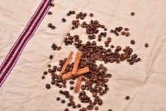 Granos de café con los palillos de canela en textura del vintage Co asado Imagen de archivo libre de regalías