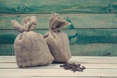 Granos de café con los sacos de la arpillera Imagen de archivo