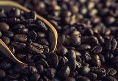 Granos de café con una cucharón de madera Fotos de archivo libres de regalías