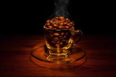 Granos de café de oro en una taza con humo Imágenes de archivo libres de regalías