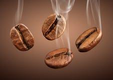 Granos de café del primer que caen con humo en fondo marrón Fotos de archivo