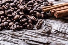 Granos de café derramados en una tabla de madera muy vieja con canela Fotografía de archivo libre de regalías